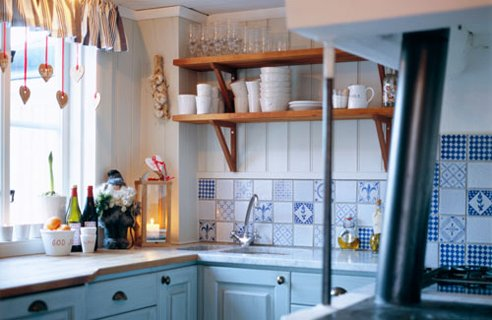 una piccola cucina blu e bianca con ripiani aperti, un backsplash di piastrelle stampate luminose, controsoffitti butcherblock sembra carino