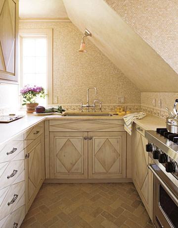 una piccola cucina di ispirazione francese con eleganti armadi geometrici, tessere di mosaico e una lampada da soffitto