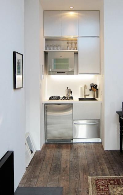 una cucina minimalista molto piccola con mobili eleganti, elettrodomestici integrati e luci integrate