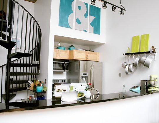una piccola cucina bianca con tutti gli elettrodomestici necessari e un bancone bar per cucinare e mangiare