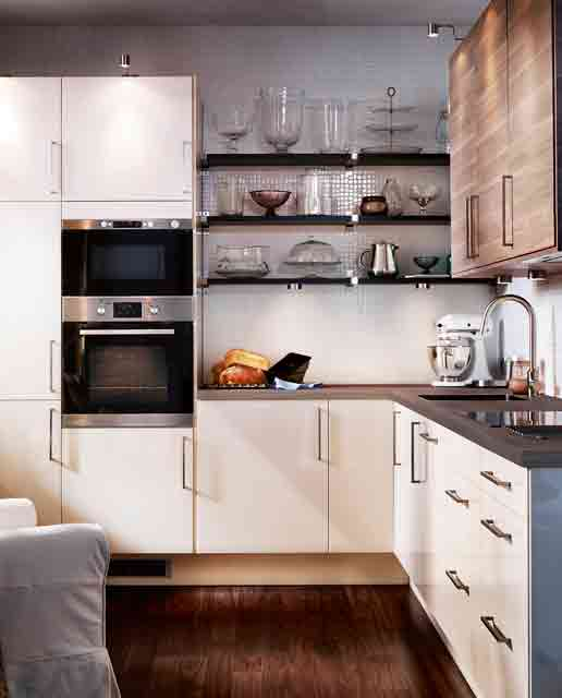 una piccola cucina bianca con piani di lavoro macchiati di scuro, mensole macchiate di scuro ed elettrodomestici da incasso è incredibile