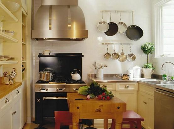 una cucina rustica dai colori caldi con ripiani in metallo, armadi e scaffali incorporati, una grande cappa e un tavolino con sgabelli rossi