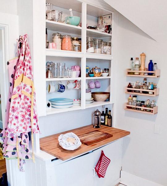 una minuscola cucina bianca con un mobile aperto con ripiani, un piano di lavoro in macelleria e alcuni ripiani per riporre le cose sul muro