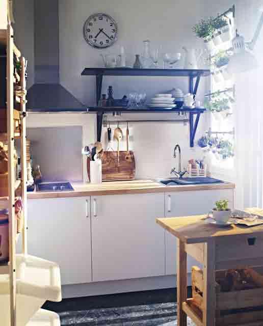 una minuscola cucina con armadietti bianchi, controsoffitti in macelleria, scaffali aperti e una cappa, più una minuscola isola da cucina e un orto verticale