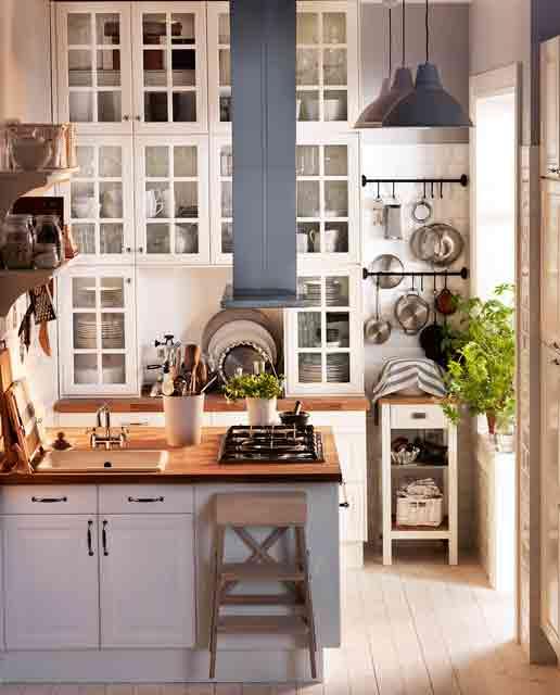 una piccola cucina bianca con doppi soffitti, l'altezza viene utilizzata per ulteriori armadietti qui, che è un'idea molto intelligente