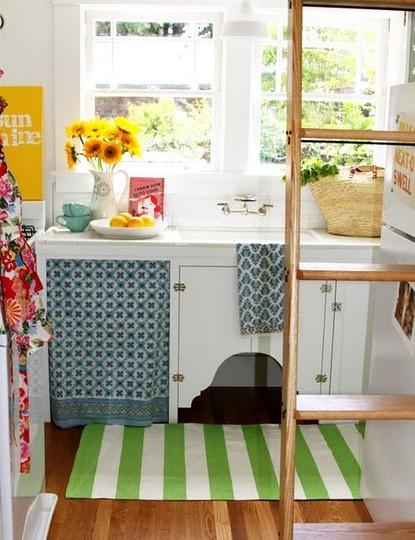 una minuscola cucina da cottage con armadi bianchi, tessuti colorati stampati, una scala per riporre le cose su e sopra