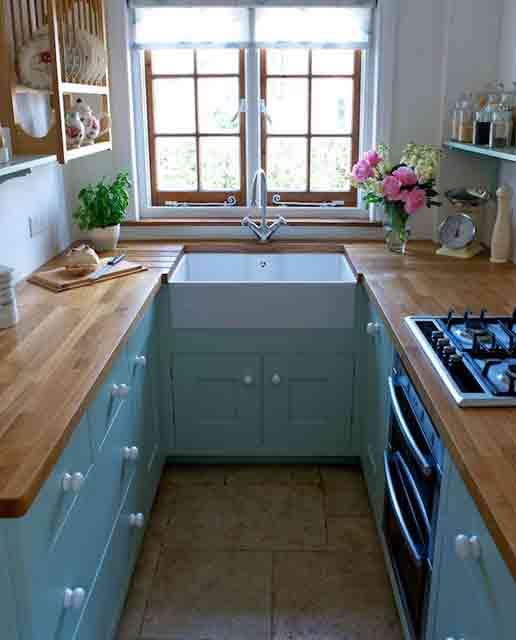 una piccola cucina blu con controsoffitti butcherblock e scaffali aperti sopra gli armadietti più una vista è accogliente e fresca