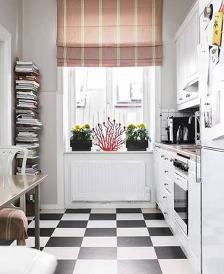 una piccola cucina bianca con pavimenti a quadri, controsoffitti in macelleria, una tenda a righe luminose e un supporto con libri è accogliente