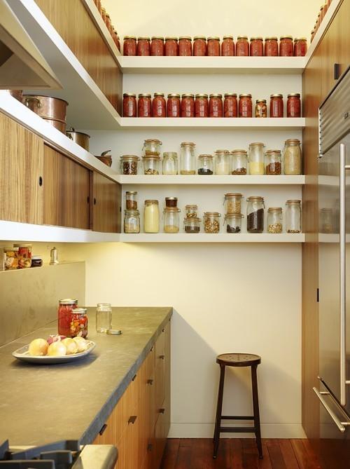 una piccola cucina minimalista con mobili in legno e ripiani in cemento, pensili e scaffali aperti per sfruttare ogni centimetro di spazio