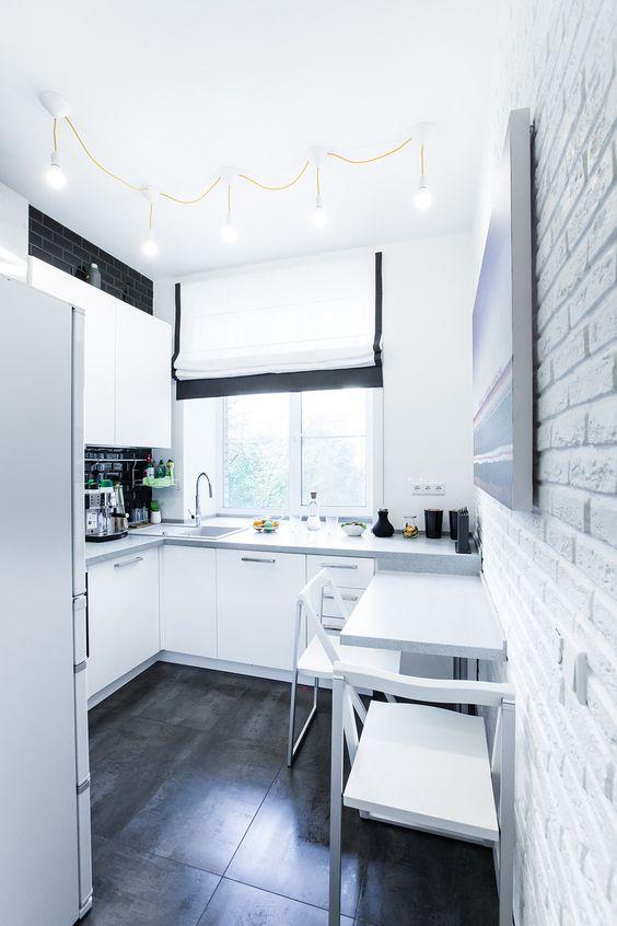 una cucina ad angolo scandinava in bianco e nero con un paraschizzi nero e una piccola zona pranzo