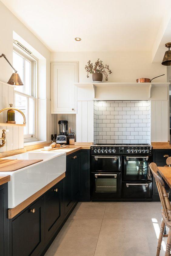 una cucina rustica nera a forma di L con controsoffitti butcherblock, un backsplash di piastrelle bianche e graziose lampade vintage è cool