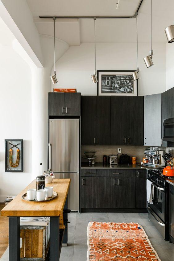 una cucina ad angolo nera con un paraschizzi in piastrelle, una piccola isola cucina con un piano di lavoro in macellaio e lampade a sospensione