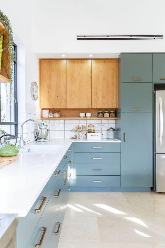 una cucina blu e chiara con un piano di lavoro bianco più un paraschizzi in piastrelle bianche e maniglie in oro e ottone