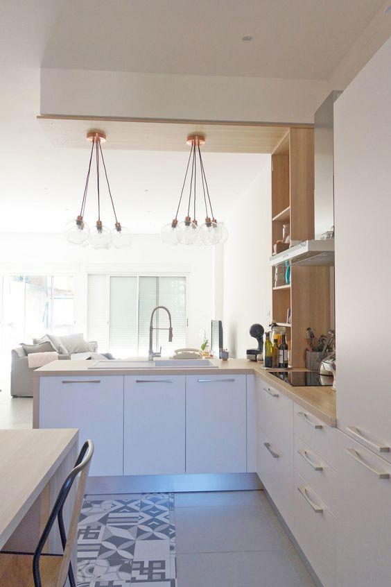 una cucina moderna ad angolo bianca con ripiani in macelleria e mensole in legno, con lampade a sospensione