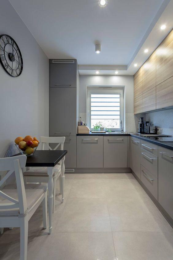 una cucina moderna ad angolo grigia e tinta chiara con ripiani neri e un piccolo spazio per mangiare