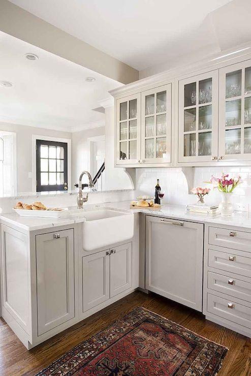 una cucina angolare da fattoria grigia a forma di L con pomelli in ottone e ripiani in pietra bianca sembra molto elegante ed elegante