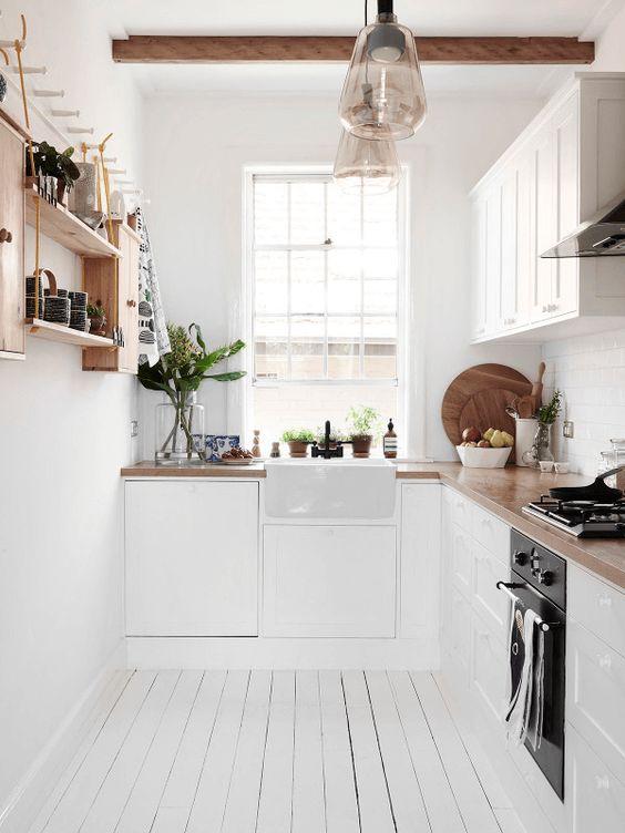 una bella cucina angolare scandinava con ripiani in macelleria, scaffali aperti e travi in legno