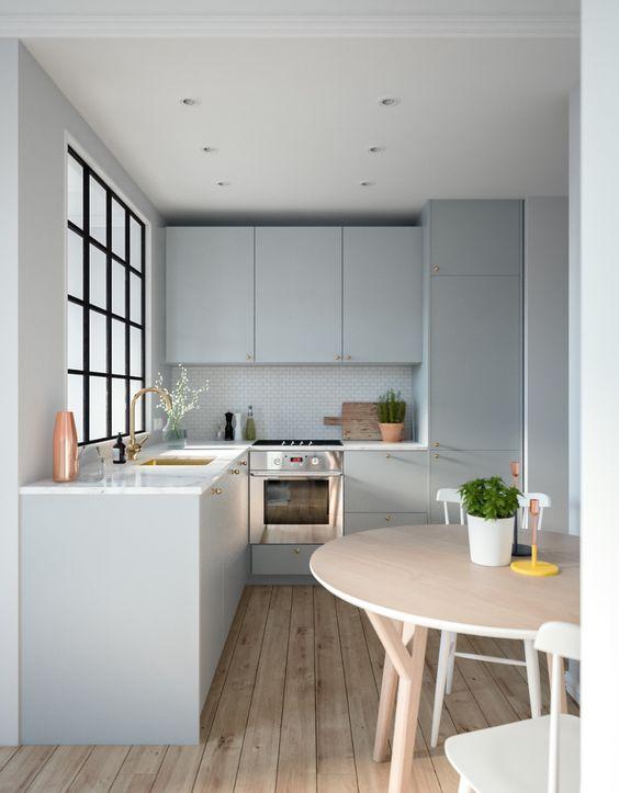 una cucina moderna ad angolo grigia con ripiani in pietra bianca, una finestra con cornice francese e un tavolo rotondo