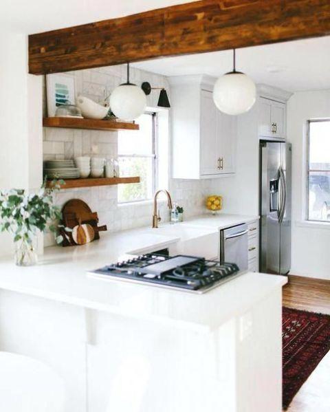 un'accogliente cucina da fattoria bianca con un paraschizzi in piastrelle di marmo bianco e una trave di legno è molto accogliente