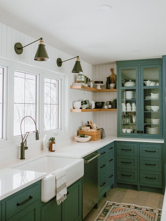 una cucina da fattoria verde con una vetrinetta, ripiani in pietra bianca e maniglie nere è uno spazio chic