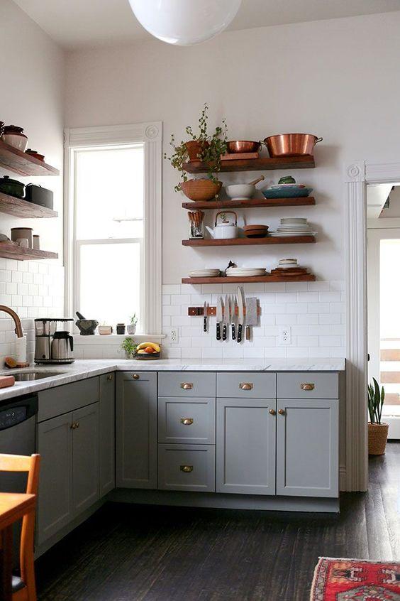 una cucina angolare boho grigia con ripiani aperti, un ripiano in pietra bianca e un paraschizzi in piastrelle bianche più vegetazione
