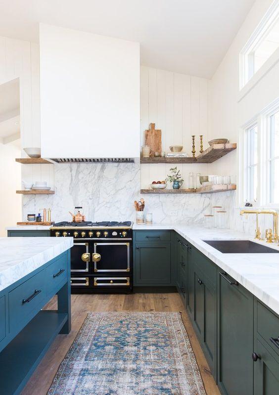 una grande cucina ad angolo blu scuro e bianca con ripiani in pietra bianca e un paraschizzi più un'isola cucina abbinata