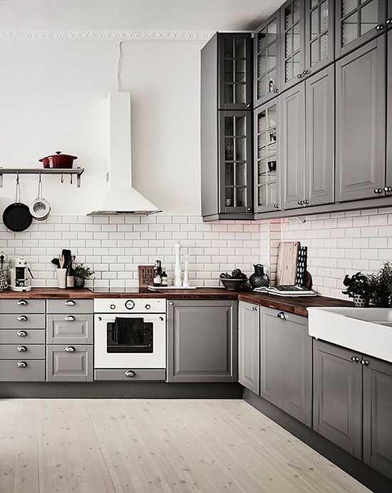 una cucina ad angolo scandinava grigia con controsoffitti in macelleria riccamente colorati e un paraschizzi in piastrelle bianche più elettrodomestici bianchi