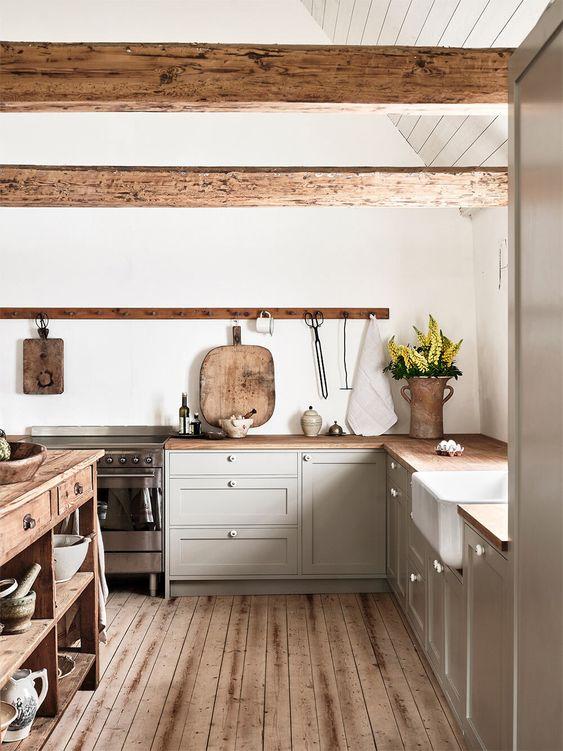 una cucina ad angolo grigio chiaro con controsoffitti e travi in legno, un'isola cucina in legno e un pavimento in legno