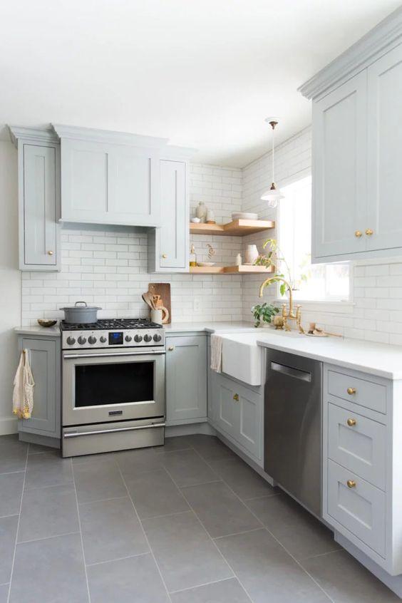 una cucina ad angolo grigio chiaro con ripiani aperti, un paraschizzi in piastrelle bianche e maniglie dorate è uno spazio molto elegante e accogliente