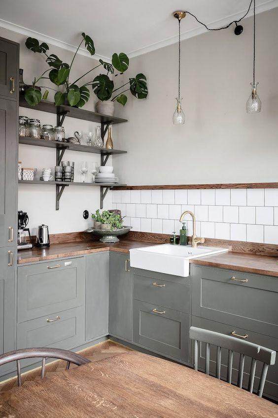 una cucina angolare rustica grigia con controsoffitti butcherblock, scaffali aperti e piante in vaso più lampade a sospensione