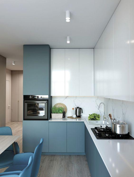 una cucina angolare minimalista blu e bianca con un paraschizzi in pietra bianca e controsoffitti bianchi è tutto chic