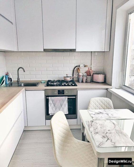 una cucina angolare minimalista a forma di L con mobili eleganti e controsoffitti butcherblock più una piccola zona pranzo