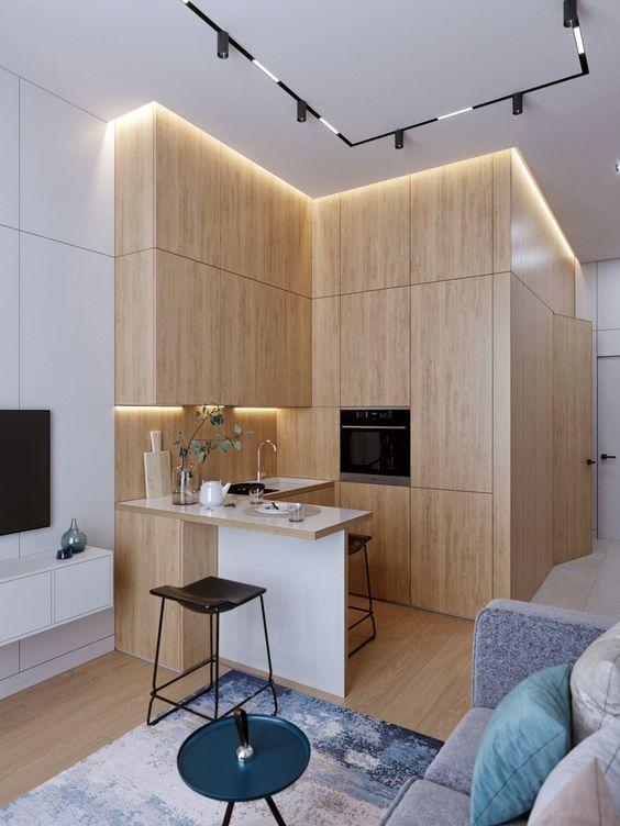 una cucina ad angolo minimalista in legno biondo con luci integrate e una piccola isola cucina è super cool