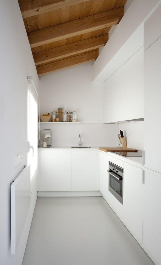 una cucina angolare minimalista bianca con soffitto e travi in legno e una finestra è molto bella e non sembra troppo piccola
