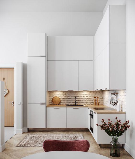 una cucina ad angolo minimalista bianca con un paraschizzi in mattoni, controsoffitti butcherblock e luci integrate