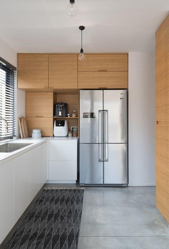 una cucina ad angolo minimalista bicolore con mobili eleganti, ripiani in pietra bianca e un tappeto stampato è molto elegante