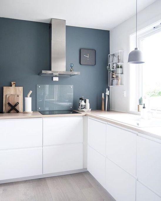 una cucina minimalista bianca a forma di L con ripiani in butcherblock, un paraschizzi in vetro e una lampada a sospensione