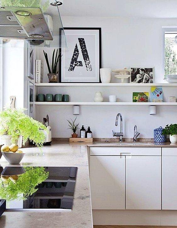 una cucina ad angolo neutra, scaffali aperti, verde e controsoffitti in pietra e finestre per la luce naturale
