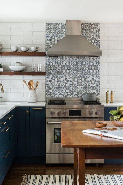 una cucina a L blu scuro con un paraschizzi in piastrelle bianche e fantasia e un tavolo in legno come isola della cucina o per consumare i pasti