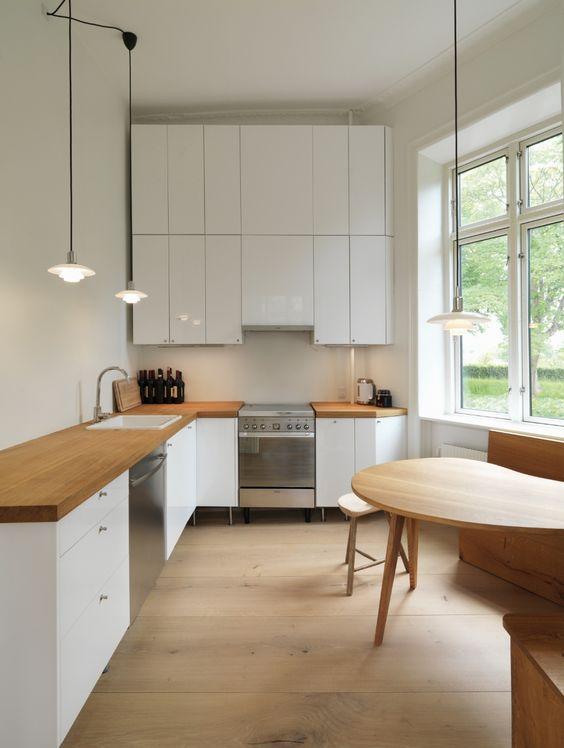 una moderna cucina angolare bianca con controsoffitti butcherblock e un elegante alzatina bianca più uno spazio da pranzo vicino alla finestra