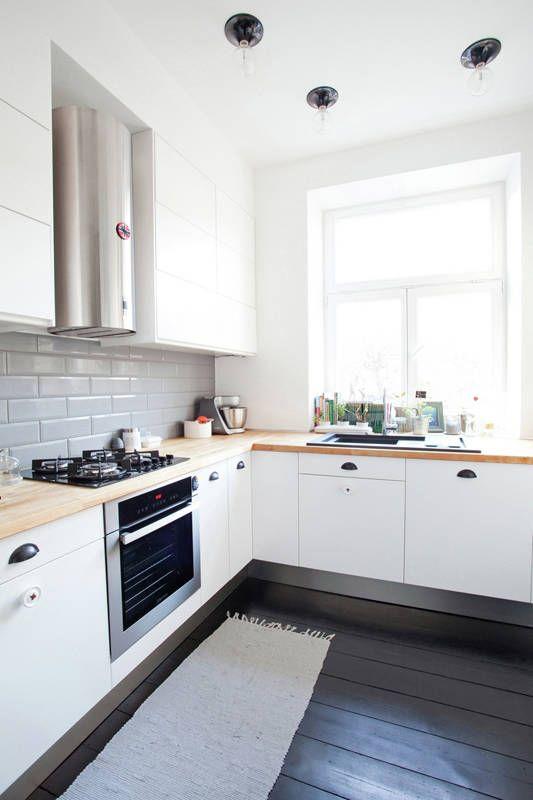 una moderna cucina ad angolo bianca con ripiani in butcherblock e un paraschizzi in piastrelle grigie più un pavimento nero