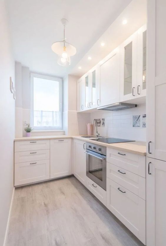 una moderna cucina angolare bianca con un paraschizzi in piastrelle bianche e controsoffitti in macellaio macchiati di luce