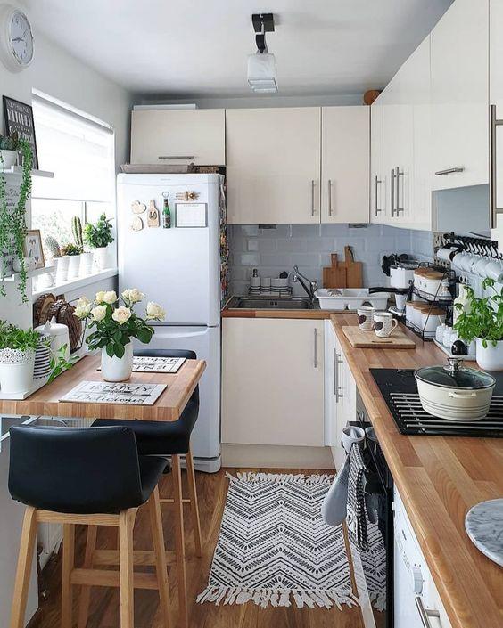 una cucina angolare neutra con piastrelle grigie, controsoffitti butcherblock e piante e fiori in vaso
