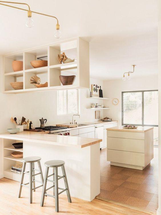 una cucina ad angolo piuttosto moderna e neutra con una mensola sospesa, una piccola isola cucina e piani di lavoro butcherblock