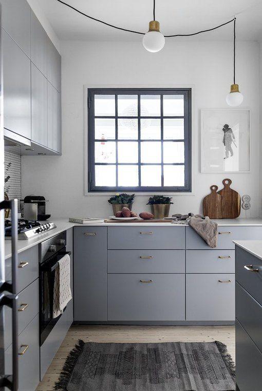 una piccola cucina angolare grigia con ripiani bianchi, una finestra con cornice nera e lampadine a sospensione