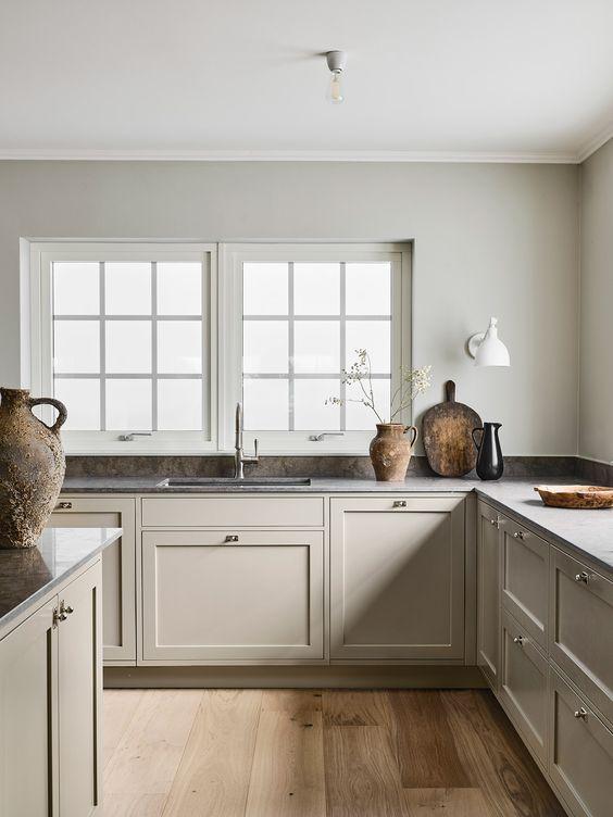 una raffinata cucina ad angolo nordica con alzatina in pietra grigia e piani di lavoro è molto calmante e rilassante