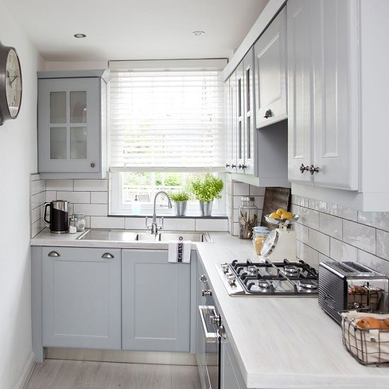 una piccola cucina ad angolo grigia con un paraschizzi in piastrelle bianche e ripiani in pietra bianca è uno spazio grazioso e accogliente