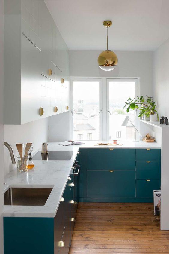 una piccola e chic cucina ad angolo color stoppa con maniglie dorate e una lampada a sospensione dorata più piante in vaso