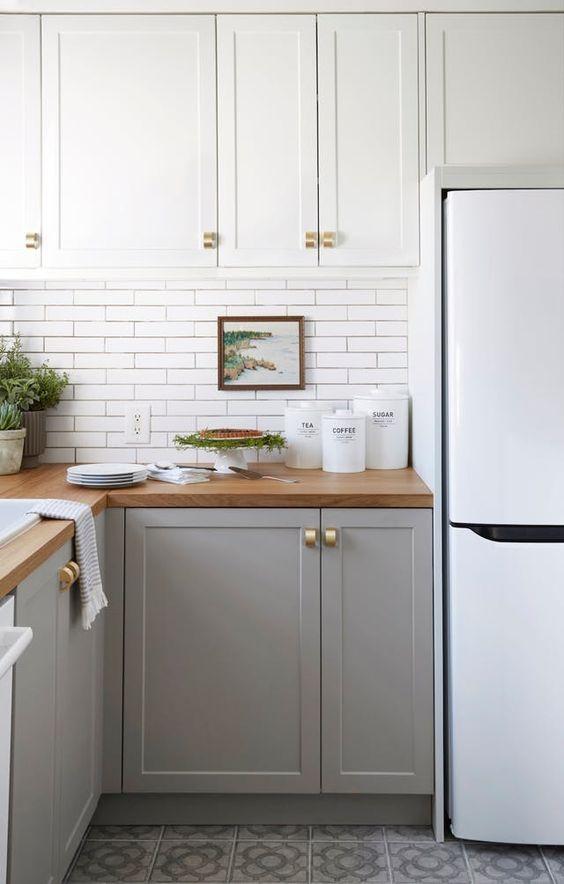 una cucina ad angolo bicolore con armadi bianchi e grigi, un paraschizzi in piastrelle bianche e tocchi dorati è puro chic
