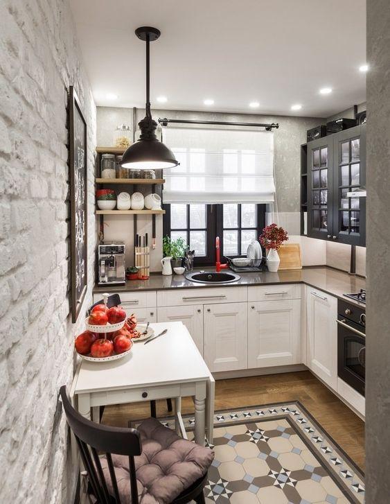 una piccola cucina ad angolo con armadi bicolore, ripiani scuri e una lampada a sospensione nera più piastrelle a motivi geometrici